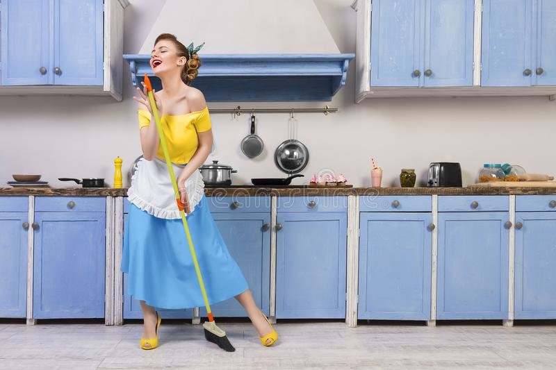 Retro pin up girl housewife in the kitchen. Retro / pin up girl woman female / housewife wearing colorful top, skirt and white apron holding mop singing and royalty free stock photos