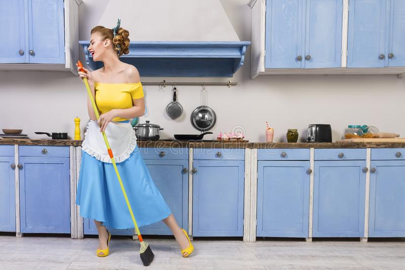 Retro pin up girl housewife in the kitchen. Retro pin up girl woman female / housewife wearing colorful top, skirt and white apron holding mop singing and royalty free stock images