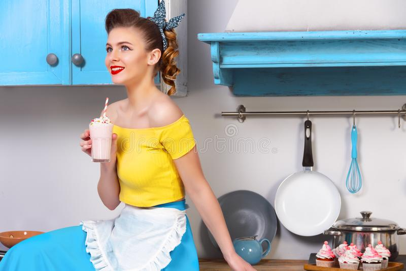 Retro pin up colorful woman housewife. Retro / pin up girl woman female housewife wearing colorful top, skirt and white apron holding sweet strawberry milkshake stock images