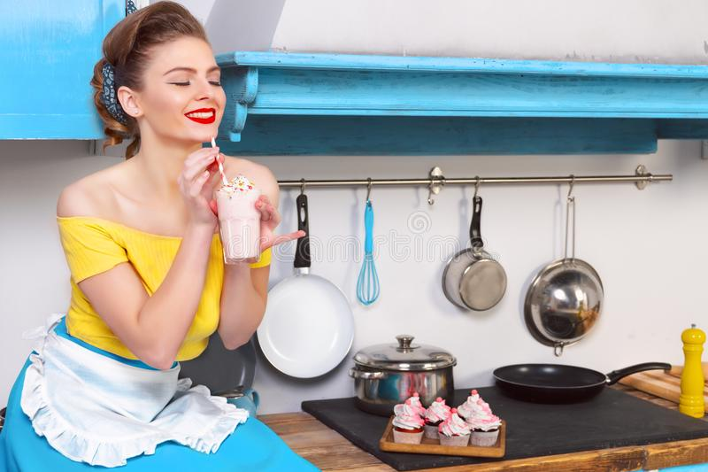 Retro pin up colorful woman housewife. Retro pin up girl woman female housewife wearing colorful top, skirt and white apron holding sweet strawberry milkshake stock images
