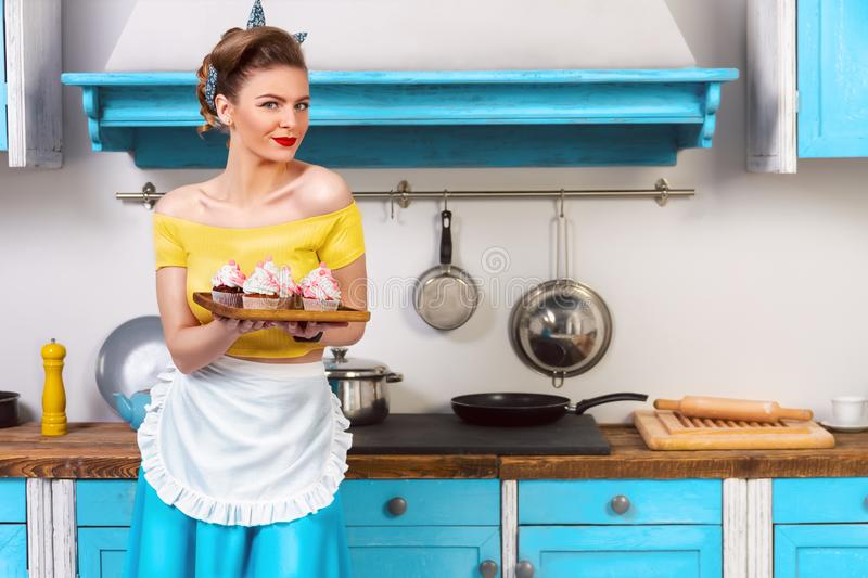 Retro pin up colorful woman housewife. Retro pin up girl woman female housewife wearing colorful top, skirt and white apron holding tray with cooked sweet stock image
