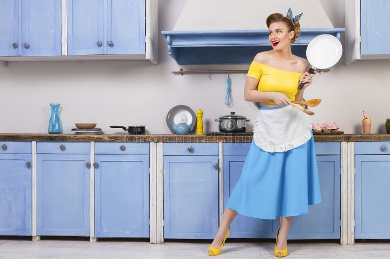 Retro pin up girl housewife in the kitchen. Retro pin up girl woman female housewife wearing colorful top, skirt and white apron and yellow high heels holding stock photography