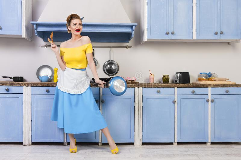 Retro pin up girl housewife in the kitchen. Retro pin up girl woman female housewife wearing colorful top, skirt and white apron and yellow high heels royalty free stock photography