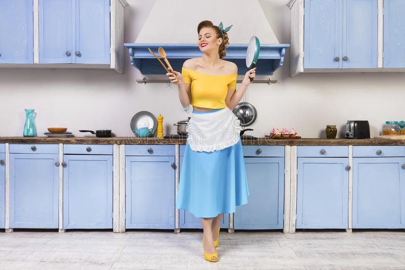 Retro pin up woman housewife sitting in the kitchen stock image