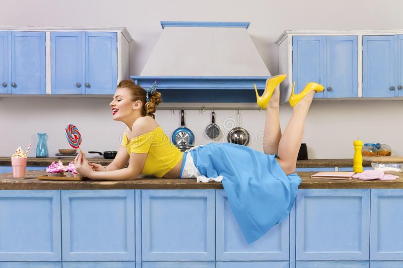 Retro pin up girl woman lying relaxing on kitchen stock photography