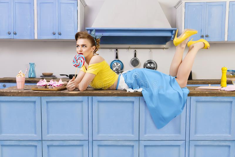 Retro pin up girl woman lying relaxing on kitchen. Retro pin up girl woman female housewife wearing yellow top, blue skirt and white apron lying relaxing with royalty free stock photos