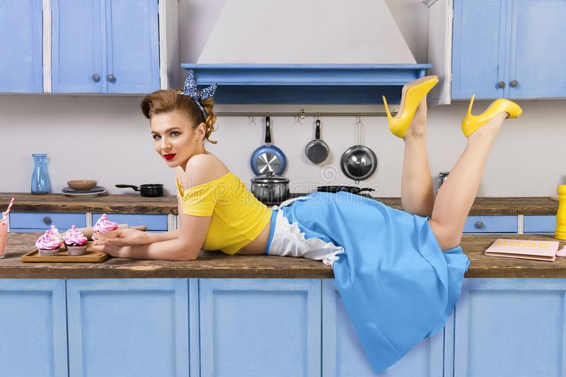 Retro pin up girl woman lying relaxing on kitchen royalty free stock photography