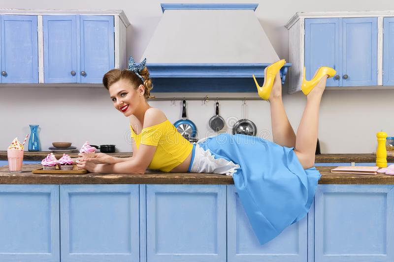 Retro pin up girl woman lying relaxing on kitchen stock image