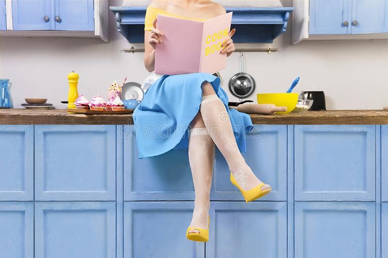 Retro pin up girl woman sitting on kitchen and reading pink cook book stock image