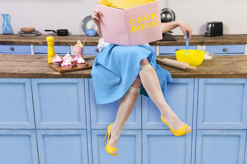 Retro pin up girl woman sitting on kitchen and reading pink cook book stock photos