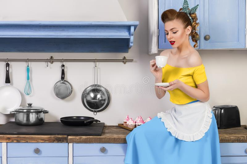 Retro pin up woman housewife sitting in the kitchen. Retro pin up girl woman female housewife wearing colorful top, skirt and white apron holding and drinking stock images