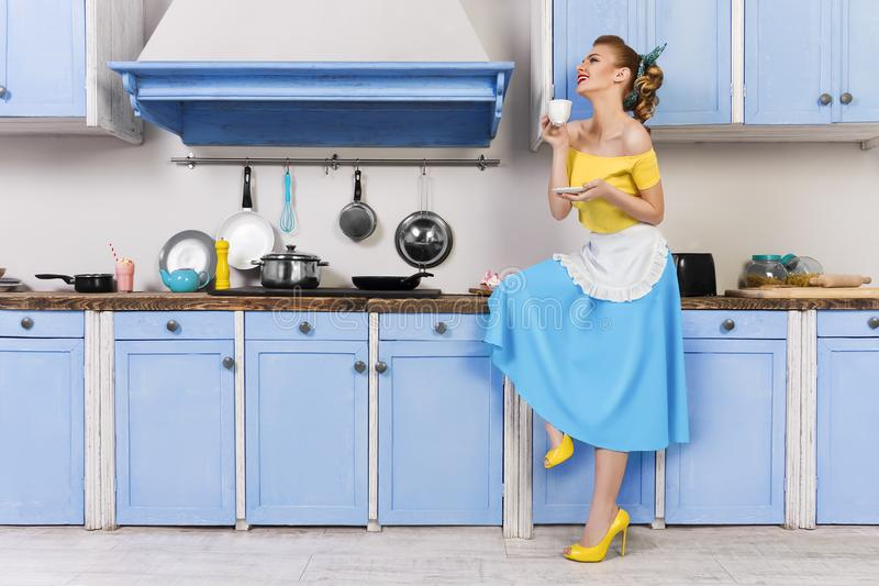 Retro pin up woman housewife sitting in the kitchen royalty free stock image
