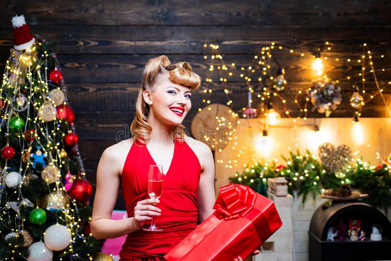 Retro pin-up woman posing on vintage wooden Christmas background. Merry Christmas and happy new year. Young woman in. Elegant red dress over Christmas interior stock photography