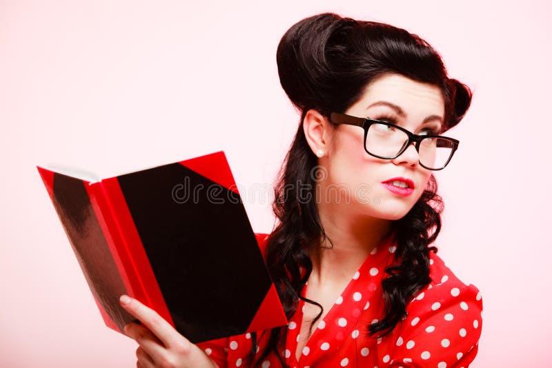 retro Pinupmädchen im Brillenlesebuch lizenzfreies stockfoto