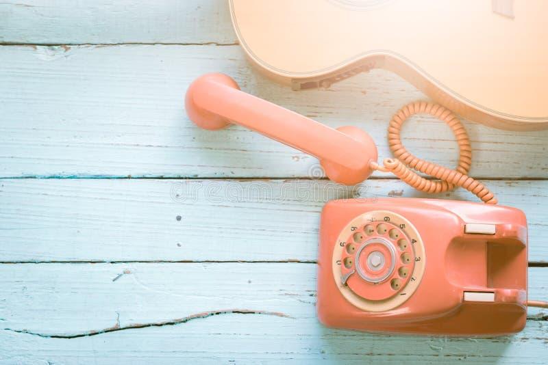 Retro pomarańczowoczerwony telefon i gitara zdjęcie stock