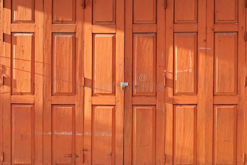 Retro porta di piegatura di legno tailandese arancio con la serratura nell'ambito di luce solare di sera immagini stock libere da diritti