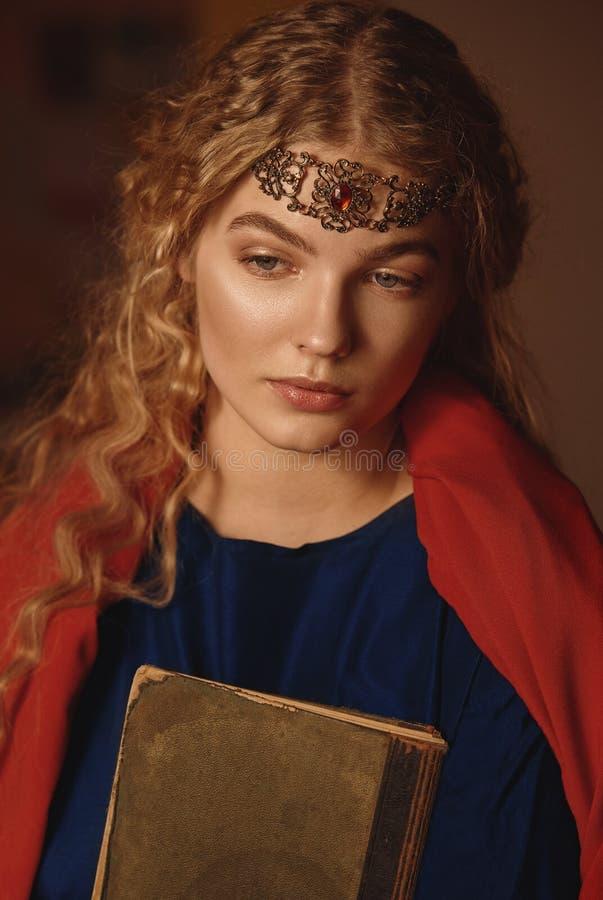 Retro- Porträt einer schönen träumerischen jungen Frau, die draußen ein Buch in den Händen hält Weiches Weinlesetonen stockfotografie