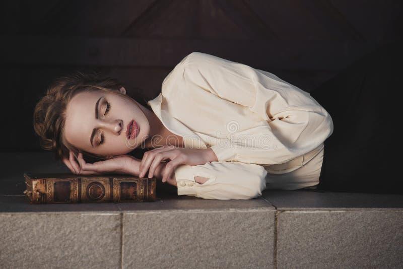 Retro- Porträt eines schönen träumerischen Mädchens, das draußen auf dem Buch schläft Weiches Weinlesetonen lizenzfreie stockfotografie