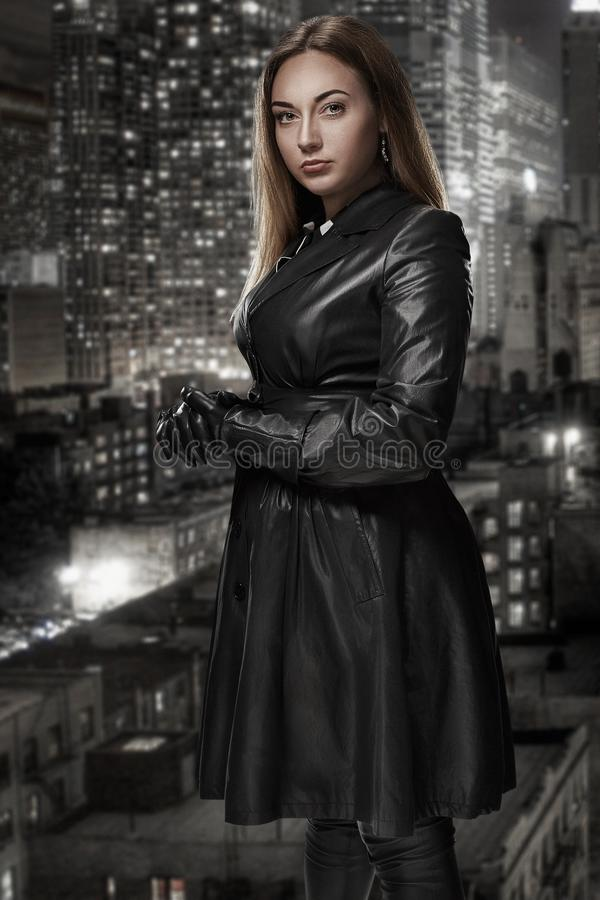 Retro portrait of inaccessible beautiful woman in black cloak stands against the background of the night city. Film noir. Vintage Hollywood style. Studio shot stock photos