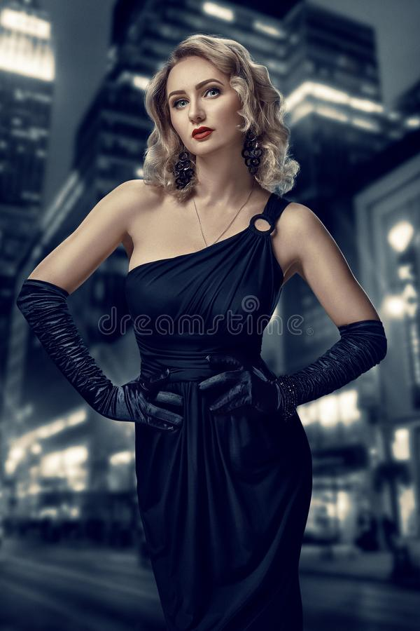 Retro portrait of inaccessible beautiful woman in black dress with red lips, smokey eyes and long earrings stands royalty free stock photography