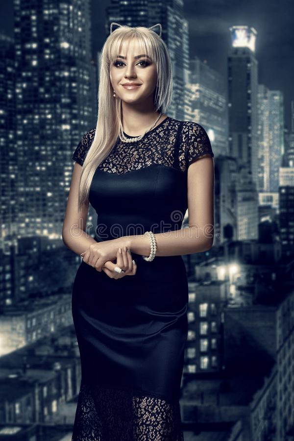 Retro portrait of inaccessible beautiful woman in black dress with smokey eyes and necklace stands against the stock images