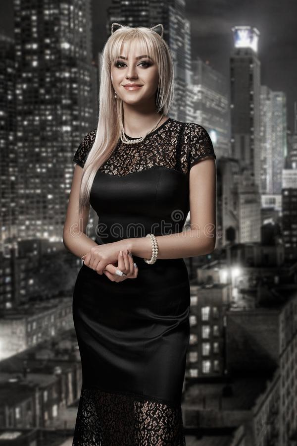 Retro portrait of inaccessible beautiful woman in black dress with smokey eyes and necklace stands against the royalty free stock photo