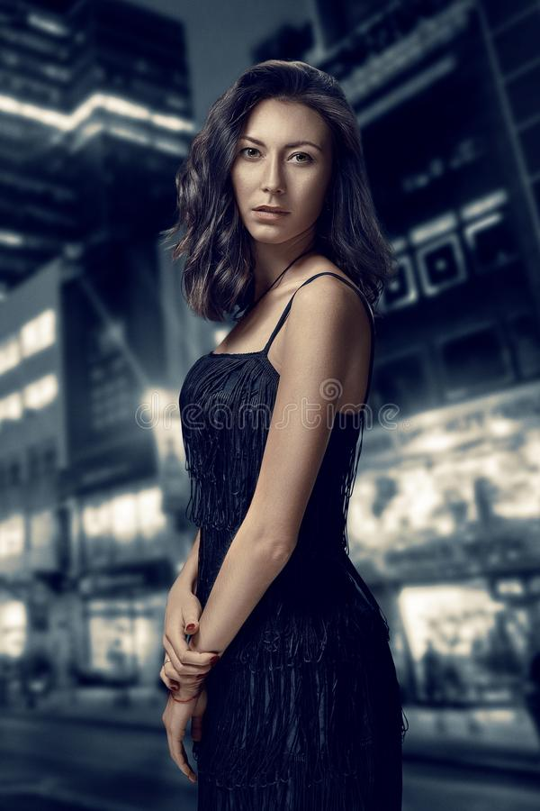 Retro portrait of inaccessible beautiful woman in black dress stands against the background of the night city. Film noir stock photography