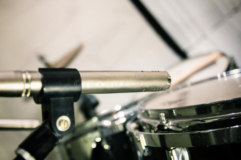Retro professional microphone placed close to drums with sticks stock photos
