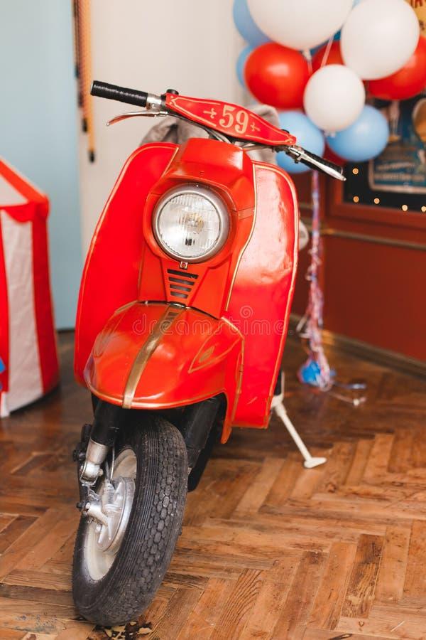 Retro röd sparkcykel i oldschooltappning som är inre med luftballonger royaltyfri foto