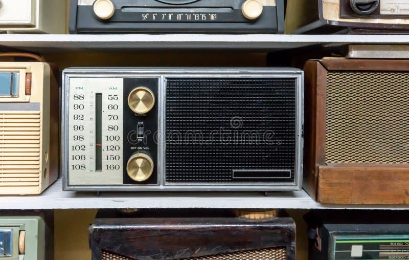 Retro radioricevitori di radiodiffusione sullo scaffale di legno contro fondo giallo immagine stock libera da diritti
