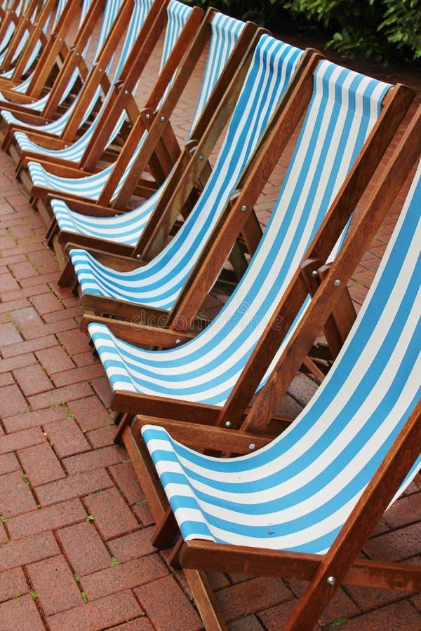 Retro randiga solstolar för strandstiltappning royaltyfri foto