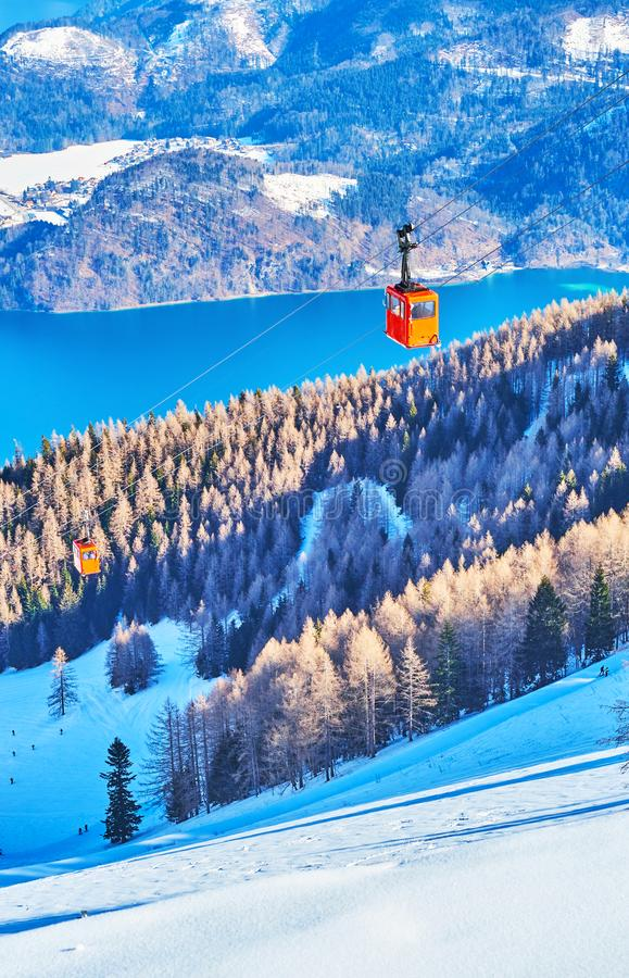 Retro red gondola of Zwolferhorn cableway, St Gilden, Salzkammergut, Austria. The vintage red gondola of Zwolferhorn air lift, riding over the snowy mountain royalty free stock photo