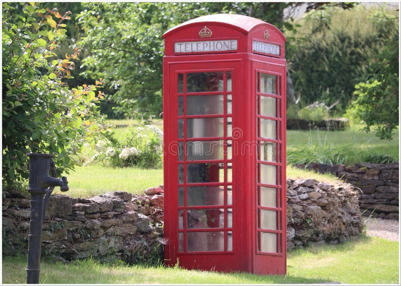 Retro red phone box in a country lane. Royal creat on top. Red English phone box , retro style red box in a country lane Warwickshire stock photos