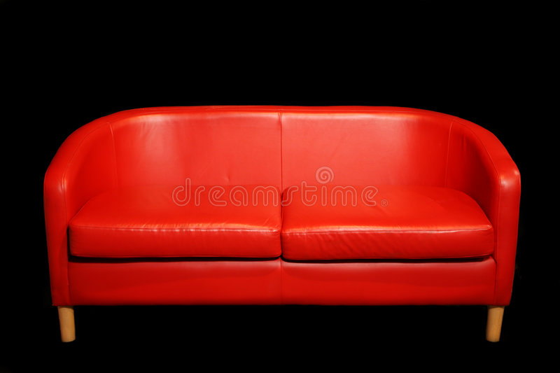 Retro Red Sofa in dark room. Retro fifties sixties style red sofa settee against dark wall royalty free stock images