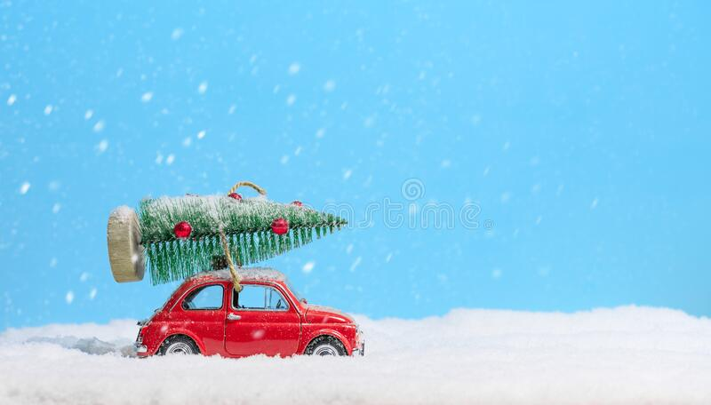Retro red toy car carrying christmas tree on roof in the snow on blue background. Christmas background. Holidays card. Toy red car no name carrying christmas royalty free stock photo