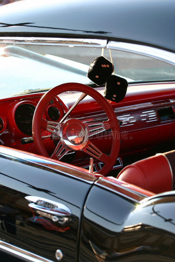 Retro Ride. Get behind the wheel of this exquisite classic, fully restored American car. Selective focus is on the red steering wheel/dash. Complete with black royalty free stock image