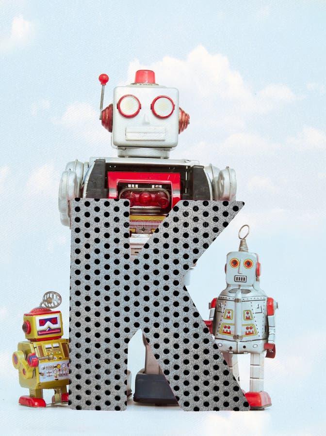 Retro robots die een grote metaalbrief K met blauwe hemel houden royalty-vrije illustratie