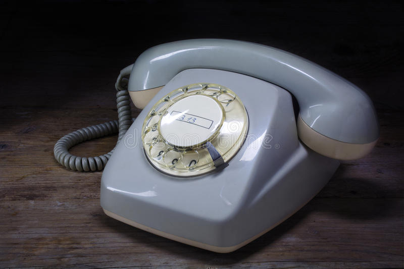 Retro rotary telephone of gray plastic with rotary dial on a dar. Old-fashioned telephone of gray plastic with rotary dial on a dark wooden table stock photography