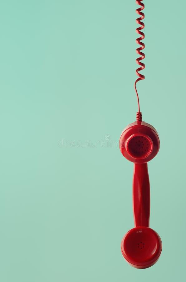 Retro- roter Telefonhörer, der durch gewundene Schnur auf Aqua Back hängt lizenzfreie stockfotografie