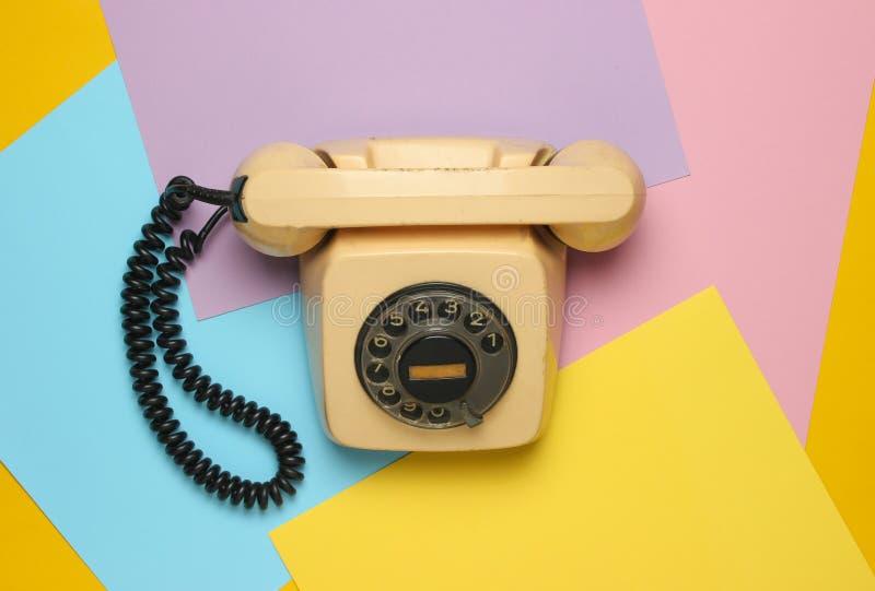 Retro roterande telefon från 80-tal på en kulör pastellfärgad bakgrund Bästa sikt, minimalism royaltyfri bild