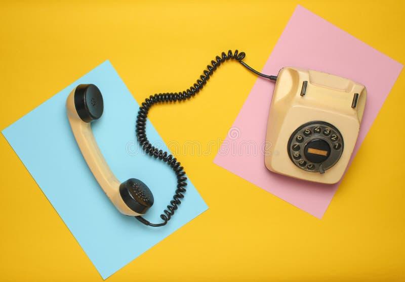 Retro roterande telefon från 80-tal på en kulör pastellfärgad bakgrund Bästa sikt, minimalism arkivbild