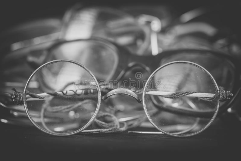Retro round spectacles close up, monochrome effect. Heap of scratched and broken eyeglasses. Repairing and replacing old royalty free stock photos