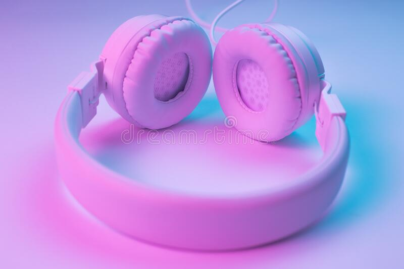 Retro 90s style photo of white stylish wireless headphone in neon lights. Music concept. Retro 90s style photo of white stylish wireless headphone in neon stock photos