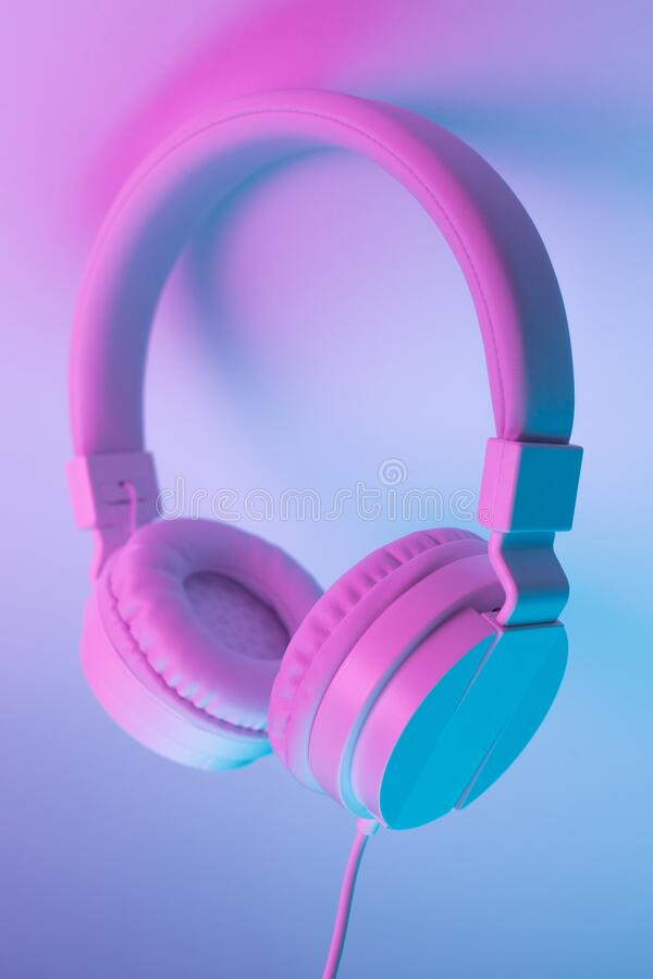 Retro 90s style photo of white stylish wireless headphone in neon lights. Music concept. Retro 90s style photo of white stylish wireless headphone in neon royalty free stock image