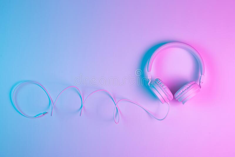 Retro 90s style photo of white stylish wireless headphone in neon lights. Music concept. Retro 90s style photo of white stylish wireless headphone in neon royalty free stock photography