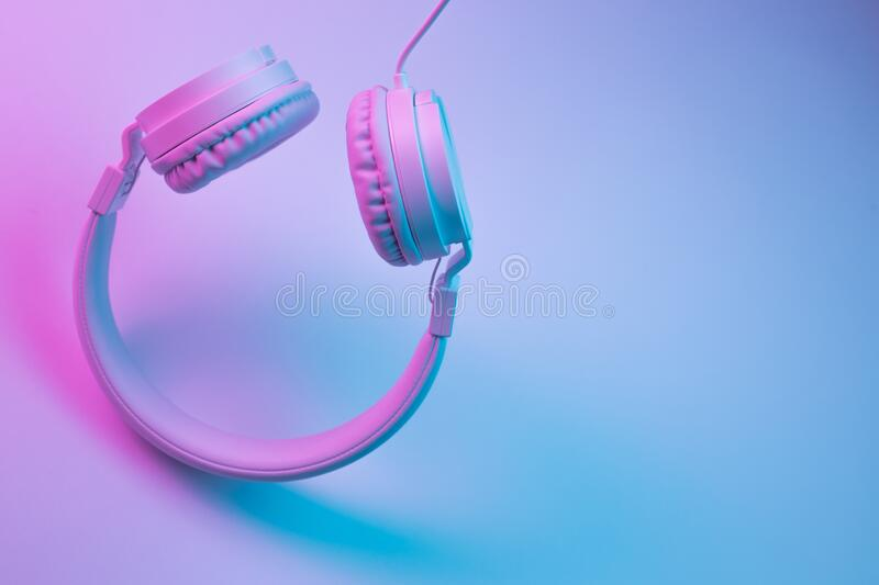 Retro 90s style photo of white stylish wireless headphone in neon lights. Music concept. Retro 90s style photo of white stylish wireless headphone in neon royalty free stock photo