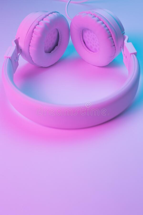 Retro 90s style photo of white stylish wireless headphone in neon lights. Music concept. Retro 90s style photo of white stylish wireless headphone in neon royalty free stock images