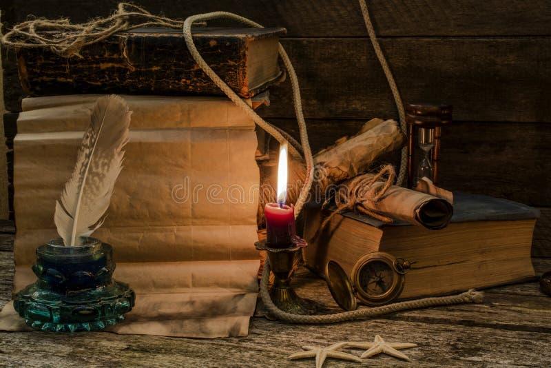 Retro sammans?ttning med gamla dokument, b?cker, den br?nnande stearinljuset och och bl?ckhornen Utrymme f?r text arkivfoto