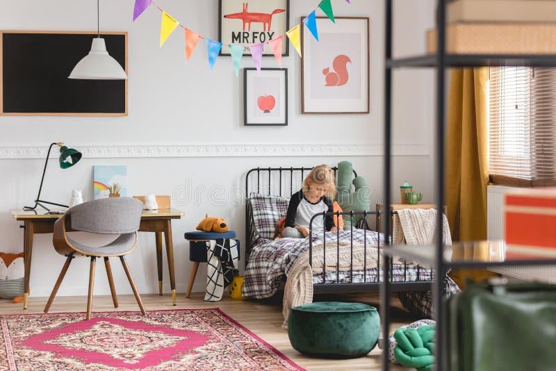 Retro- Schlafzimmer für Kind mit dem Schulmädchen, das auf Metalleinzelbett sitzt stockfotografie