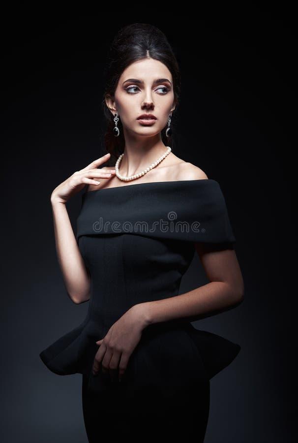 Retro schot van mooie jonge vrouw in studio Uitstekend portret van mooi meisje in jaren '60stijl Schitterende dame in zwarte kled royalty-vrije stock foto